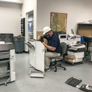 Office Systems team member repairing a copier
