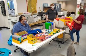 Office Systems team members organizing backpacks for local charities