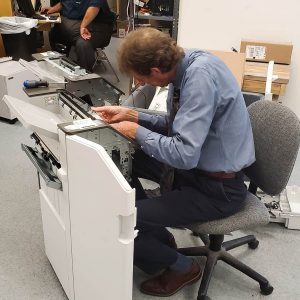 Office Systems team member working on repairs