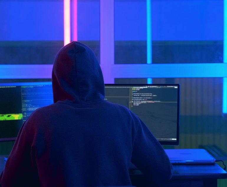 Back view of hacker in a black jacket