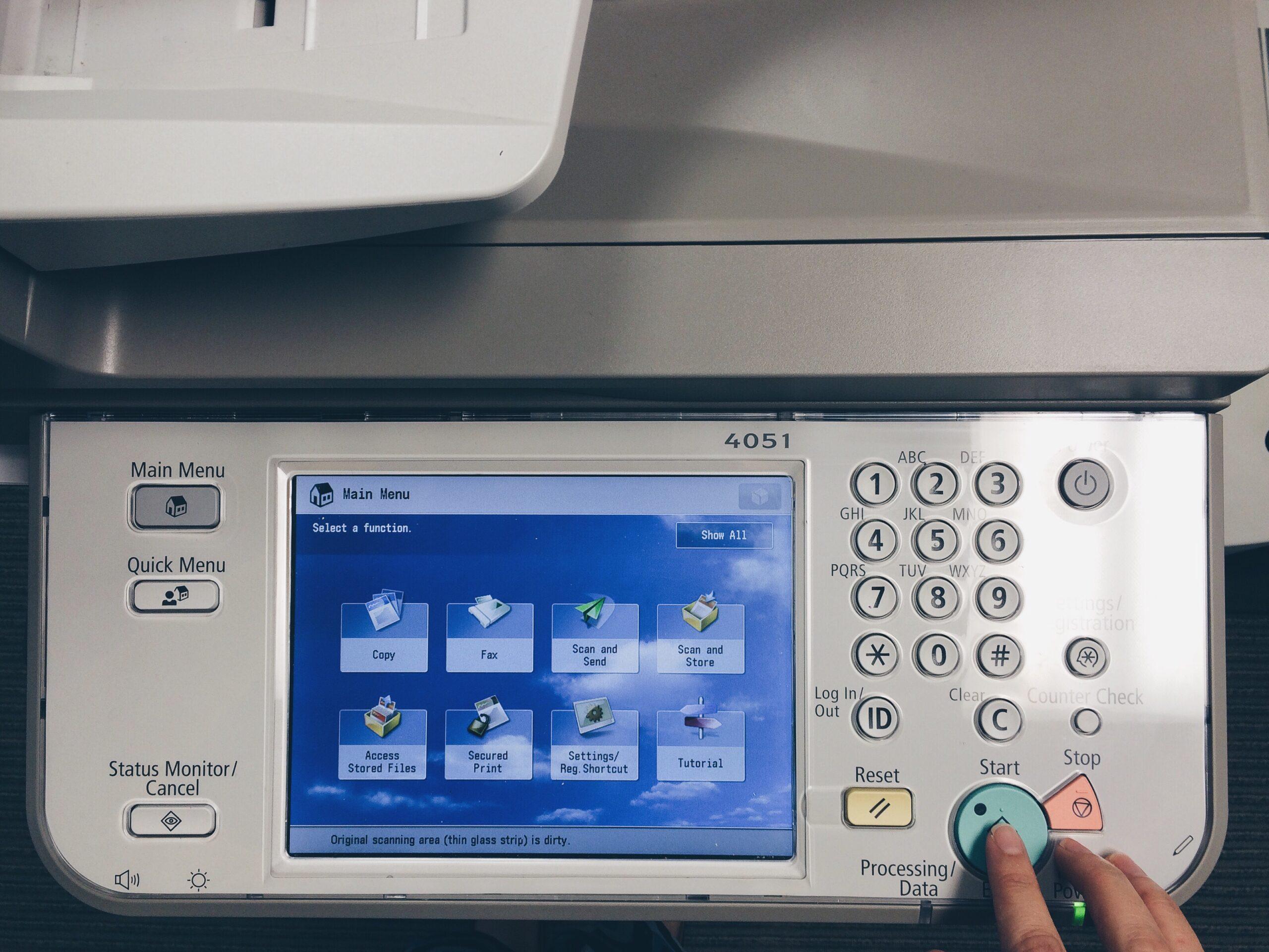 Worker pressing start on a printer